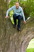 Blonder Mann steht auf einem Baum und springt nach unten