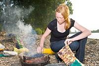 Junge Frau bereitet einen Grill am Ufer des Rheins vor