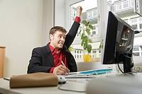 Mann am Schreibtisch vor dem Computer mit Grafiktablett ballt die Faust und jubelt