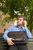 Mann in Businesskleidung sitzt auf einer Parkbank und hört Musik über Kopfhörer