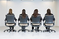 Rear view of four business women sitting on office chairs.