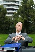 Geschäftsmann sitzt in einem Park an einem Schreibtisch und schaut auf seine Armbanduhr