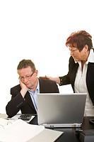 Frau tröstet ihren traurigen Kollegen am Schreibtisch