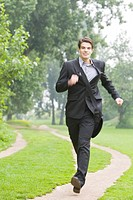 Junger Geschäftsmann läuft im Park