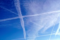 Morning blue sky with white contrails of jet aircraft