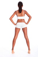 Rear view of a beautiful healthy young african american woman wearing white sports underwear, standing against white background showing off fit body.