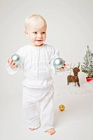 Baby girl holding Christmas ornaments