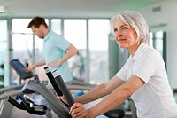 Older woman using treadmill in gym