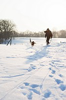 Man walking dog in snowy field