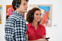 Young couple using audio guides in art gallery