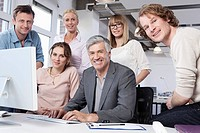 Germany, Bavaria, Munich, Men and women using computer in office, smiling, portrait
