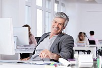 Germany, Bavaria, Munich, Mature man smiling, colleagues working in background