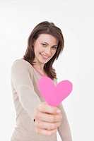 Young woman holding heart shape, smiling