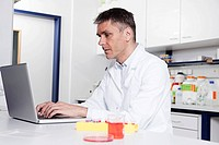 Germany, Bavaria, Munich, Scientist using laptop in laboratory