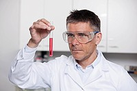 Germany, Bavaria, Munich, Scientist holding red liquid in test tube for medical research in... (thumbnail)