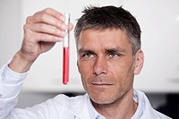 Germany, Bavaria, Munich, Scientist holding red liquid in test tube for medical research in laboratory