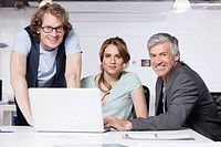 Germany, Bavaria, Munich, Men and woman with laptop in office, portrait