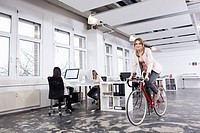 Germany, Bavaria, Munich, Woman cycling in office while colleagues working