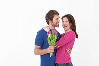 Woman holding flowers and hugging man
