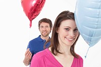 Couple with heart shaped balloons, smiling