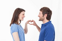 Couple making heart shape, smiling