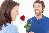 Man giving red rose to woman, smiling