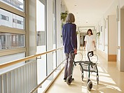Germany, Cologne, Senior women holding walking frame in corridor, caretaker in background