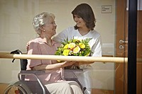 Germany, Cologne, Caretaker giving bouquet to senior women on wheelchair in nursing home