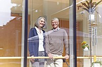 Germany, Cologne, Senior couple looking through window, smiling