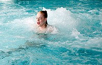 Young woman swimming in spa pool