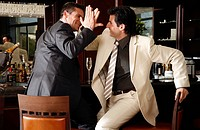 Two men slapping hands in agreement at a bar (thumbnail)