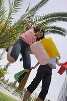 Women with shopping bags jumping (thumbnail)