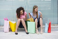 Two women sitting with shopping bags (thumbnail)