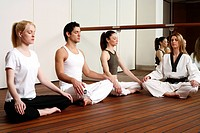 Participants in a fitness class meditating