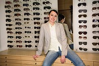 Woman posing in front of sunglasses display