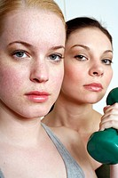 Two young women with dumbbell