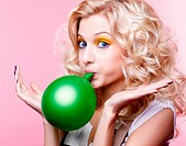 portrait of beautiful blonde party girl blowing up green balloon