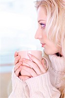portrait of beautiful blonde girl in pullover drinking coffee in the morning