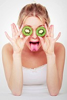 Young woman covered her eyes with pieces of kiwi and sticking out tongue