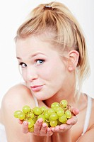 Young woman holding grapes, portrait