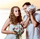 Bride and groom listening seashell music on a beach