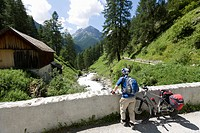 Switzerland, Mature man standing with bicycle