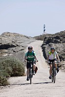 Spain, Menorca, Man and woman cycling, Cap de Favaritx in background