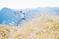 Austria, Salzburg County, Young woman with nordic walking pole and jumping in alpine meadow