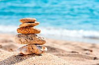 Stone tower in sand against sea. Concept for rest, spa, relaxation, resorts.