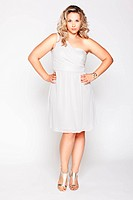 full_length portrait of beautiful plus size curly young blond woman posing on gray in white dress and court shoes