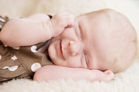 A closeup of a sleeping three week old baby girl smiling, soft focus