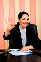 Beautiful happy business woman formal wear sitting at desk in office and showing okay hand sign