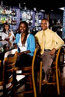 Young African couple sitting at the bar in a restaurant