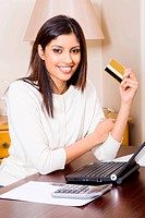confident young woman holding credit card doing online shopping